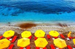 Η τοπ άποψη καρεκλών και ομπρελών ήλιων σχετικά με την πολύχρωμη κόκκινη άσπρη άμμο στρώνει με άμμο την παραλία στην Κρήτη, Ελλάδ στοκ εικόνες