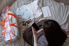 Η τοπ άποψη της εγκύου γυναίκας συλλέγει τα πράγματα σε μια τσάντα για τη γέννηση του καταλόγου παιδιών στο smartphone, κομπινεζό στοκ εικόνα