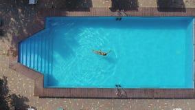 Η τοπ άποψη της λεπτής νέας γυναίκας στο μπικίνι επιπλέει στο κρύσταλλο - καθαρίστε το νερό απόθεμα βίντεο