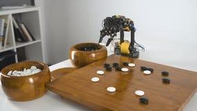 Η τοπ άποψη του βραχίονα ρομπότ με το παιχνίδι κινέζικα πηγαίνει παιχνίδι Πείραμα με τον ευφυή χειριστή Βιομηχανικό πρότυπο ρομπό φιλμ μικρού μήκους