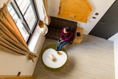 Η τοπ άποψη του κινητού τηλεφώνου εκμετάλλευσης γυναικών και εξετάζει το παράθυρο Στοκ εικόνες με δικαίωμα ελεύθερης χρήσης