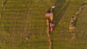Η τοπ άποψη του τρακτέρ συλλέγει το σανό από τον τομέα στοκ φωτογραφίες