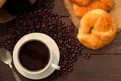 Η τοπ άποψη του φλυτζανιού καφέ και τα φασόλια καφέ σε ένα ξύλινο υπόβαθρο γνωρίζουν Στοκ Φωτογραφία