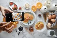 Η τοπ άποψη του χεριού που πήρε την τηγανίτα με το smartphone στον πίνακα Διδακτική φωτογραφία τροφίμων, τρόπος ζωής Α σε κοινωνι στοκ φωτογραφία