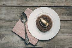 Η τοπ άποψη του χρυσού αυγού Πάσχας στη φωλιά στο άσπρο πιάτο, η πετσέτα και ο τρύγος μετακινούν με το κουτάλι στον ξύλινο πίνακα Στοκ Εικόνες