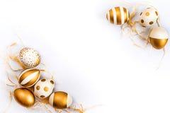 Η τοπ άποψη των αυγών Πάσχας που χρωματίζονται με το χρυσό χρώμα μέσα τα σχέδια Διάφορα ριγωτά και διαστιγμένα σχέδια Άσπρη ανασκ Στοκ Φωτογραφία