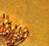 Η τοπ εικόνα άποψης της σγουρής χρυσής κορδέλλας πέρα από κατασκευασμένο ακτινοβολεί υπόβαθρο Στοκ Φωτογραφία
