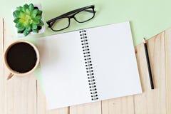 Η τοπ εικόνα άποψης του ανοικτού σημειωματάριου με τις κενές σελίδες και ο καφές κοιλαίνουν στο ξύλινο υπόβαθρο, έτοιμο για να πρ Στοκ Εικόνα