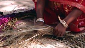 Η του Μπαγκλαντές κυρία που φορά το παραδοσιακό φόρεμα υφαίνει το φλοιό μπαμπού παράγοντας το χαλί μπαμπού σε Tangail, Μπανγκλαντ φιλμ μικρού μήκους