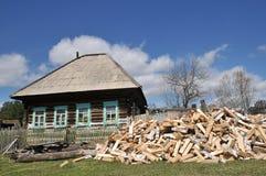 Η του χωριού ζωή πελέκησε το καυσόξυλο σημύδων στην πύλη του παλαιού ξύλινου σπιτιού στοκ φωτογραφίες