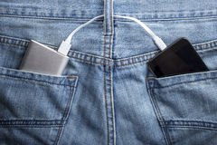 Η τράπεζα δύναμης βρίσκεται σε μια πίσω τσέπη των τζιν το κινητό τηλέφωνο charg στοκ εικόνα
