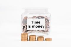 Η τράπεζα Piggy, χρυσό νόμισμα σωρών, με το χρόνο κειμένων λέξης είναι χρήματα Στοκ Εικόνες