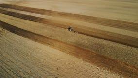 Η τρακτέρ-γεωργική μονάδα εκτελεί το όργωμα, η καλλιέργεια του χώματος του καφετιού χρώματος στον ξηρό ηλιόλουστο καιρό απόθεμα βίντεο