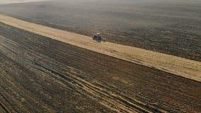 Η τρακτέρ-γεωργική μονάδα εκτελεί το όργωμα, η καλλιέργεια του χώματος του καφετιού χρώματος στον ξηρό ηλιόλουστο καιρό φιλμ μικρού μήκους