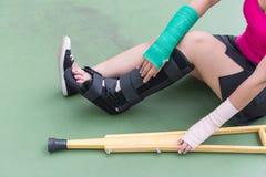 Η τραυματισμένη γυναίκα που φορά sportswear τον επίπονο βραχίονα με τον επίδεσμο γάζας, βραχίονας πέταξε και ξύλινα δεκανίκια καθ Στοκ φωτογραφία με δικαίωμα ελεύθερης χρήσης