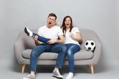 Η τρελλή ευθυμία οπαδών ποδοσφαίρου ανδρών γυναικών ζευγών κραυγής υποστηρίζει επάνω την αγαπημένη ομάδα με το πόδι λαβής σφαιρών στοκ φωτογραφία με δικαίωμα ελεύθερης χρήσης