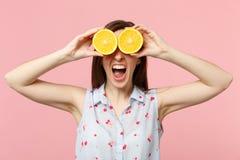 Η τρελλή κραυγάζοντας νέα γυναίκα το καλοκαίρι ντύνει την κάλυψη των ματιών με τα halfs των φρέσκων ώριμων πορτοκαλιών φρούτων στ στοκ φωτογραφία με δικαίωμα ελεύθερης χρήσης