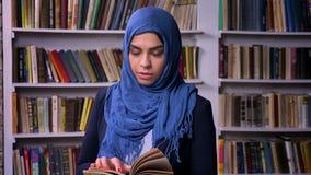 Η τρομερή αραβική γυναίκα στο σκούρο μπλε hijab κρατά το βιβλίο στη βιβλιοθήκη, που στέκεται ήρεμα και τη βέβαια ματιά στη κάμερα απόθεμα βίντεο