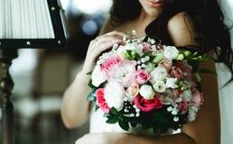 Η τρυφερή νύφη αγγίζει μια ρόδινη γαμήλια ανθοδέσμη που στέκεται στο hote Στοκ φωτογραφία με δικαίωμα ελεύθερης χρήσης