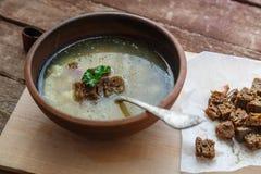 Η τσεχική σούπα σκόρδου με σπιτικά croutons κλείνει επάνω σε ένα κύπελλο στον ξύλινο πίνακα Στοκ Φωτογραφίες