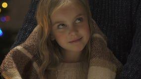 Η τυλίγοντας κόρη γονέα στο κάλυμμα, δίνει τη ζεστασιά και την άνεση στο παιδί στα Χριστούγεννα απόθεμα βίντεο