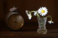 Η τυποποιημένη θολωμένη φωτογραφία μιας ανθοδέσμης ανθίζει και παλαιά ρολόγια Στοκ Εικόνες
