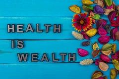 Η υγεία είναι κείμενο πλούτου στο μπλε ξύλο με το λουλούδι στοκ εικόνες