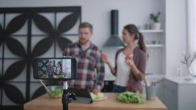 Η υγεία blog, το χαμογελώντας κορίτσι bloggers και ο ευπρόσδεκτος συνδρομητής τύπων και προετοιμάζουν τα χρήσιμα τρόφιμα με τα λα απόθεμα βίντεο