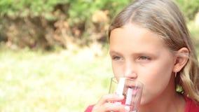 Η υγειονομική περίθαλψη φύσης μικρών κοριτσιών πίνει το νερό από ένα ποτήρι φιλμ μικρού μήκους