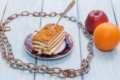 Η υγιής έννοια κατανάλωσης, ένα κομμάτι του κέικ σε έναν ξύλινο πίνακα περιβάλλεται από μια αλυσίδα μετάλλων Στοκ Φωτογραφίες