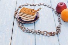 Η υγιής έννοια τροφίμων, ένα κομμάτι του κέικ σε έναν ξύλινο πίνακα περιβάλλεται από μια αλυσίδα σιδήρου Στοκ Φωτογραφίες
