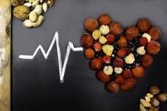 Η υγιής έννοια υγείας κατανάλωσης και καρδιών με μια καρδιά διαμόρφωσε με τα βακκίνια, σμέουρα, φράουλες, καρύδια, πλήρη των βιτα στοκ εικόνα