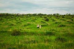 Η υγιής αγροτική ζωή Η γυναίκα και ο άνδρας στον πράσινο τομέα Στοκ Φωτογραφία
