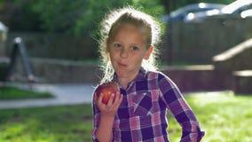Η υγιής κατανάλωση, το χαριτωμένο μικρό κορίτσι στα ελεγμένα δαγκώματα πουκάμισων και αστείος μασούν το ώριμο juicy μήλο στο back απόθεμα βίντεο