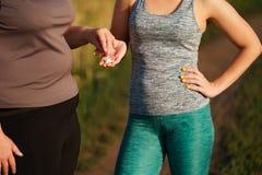 Η υπέρβαρη γυναίκα παίρνει τα χάπια αδυνατίσματος από το φίλο στοκ φωτογραφίες