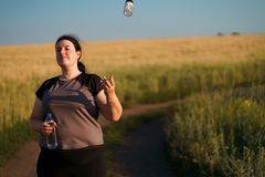 Η υπέρβαρη γυναίκα ρίχνει έξω τα χάπια αδυνατίσματος στοκ εικόνα με δικαίωμα ελεύθερης χρήσης