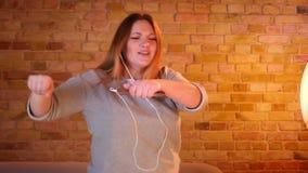 Η υπέρβαρη γυναίκα σπουδαστής ακούει τη μουσική στα ακουστικά που χορεύουν παράξενα στην άνετη εγχώρια ατμόσφαιρα απόθεμα βίντεο