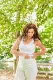 Η υπέρβαρη γυναίκα σφίγγει τους ρόλους της κοιλιάς Στοκ Φωτογραφία