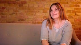 Η υπέρβαρη μακρυμάλλης γυναίκα σπουδαστής αλλάζει τα κανάλια στη TV με το μακρινό ελεγκτή στην άνετη εγχώρια ατμόσφαιρα απόθεμα βίντεο