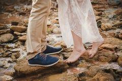 Η υπαίθρια γαμήλια τελετή, κλείνει επάνω των νέων ποδιών γυναικών που στέκονται χωρίς παπούτσια στις πέτρες μπροστά από επανδρώνε Στοκ Φωτογραφίες