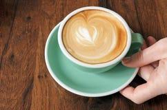 Η υπερυψωμένη άποψη του χεριού γυναικών κρατά τον επίπεδο λευκό Δρ φλιτζανιών του καφέ Στοκ Φωτογραφίες