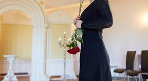 Η λυπημένη γυναίκα με το κόκκινο αυξήθηκε στην κηδεία στην εκκλησία Στοκ εικόνες με δικαίωμα ελεύθερης χρήσης
