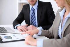 Η υπόδειξη επιχειρησιακών γυναικών στον οικονομικό αριθμό και η ομιλία με τον αρσενικό συνεργάτη της, κλείνουν επάνω των χεριών Στοκ Εικόνες