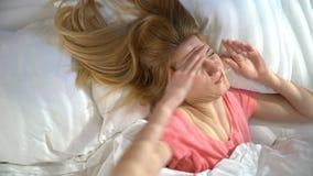 Η δυστυχισμένη νυσταλέα νέα γυναίκα δεν θέλει ξυπνήστε το πρωί και κρύψιμο κάτω από το κάλυμμα απόθεμα βίντεο