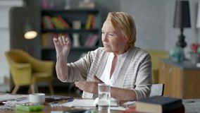 Η δυστυχισμένη προβληματική ηλικιωμένη γυναίκα εξετάζει incredulously ένα χάπι μην θελήστε να πάρετε τα ιατρικά φάρμακα απόθεμα βίντεο