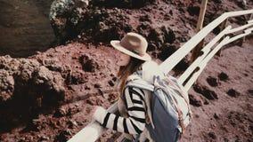 Η υψηλή άποψη γωνίας του νέου ευτυχούς θηλυκού τουρίστα με το σακίδιο πλάτης και οι αγκάλες ευρέως ανοικτές στην άκρη του ηφαιστε απόθεμα βίντεο