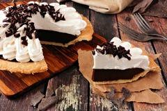 Η φέτα της πίτας κρέμας σοκολάτας, κλείνει επάνω την επιτραπέζια σκηνή ενάντια στο σκοτεινό ξύλο στοκ εικόνες