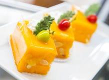 Η φέτα του ζωηρόχρωμου βαλμένου σε στρώσεις κέικ γενεθλίων που διακοσμείται με ψεκάζει Στοκ Εικόνες