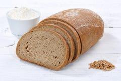 Η φέτα ψωμιού σίτου τεμαχίζει την τεμαχισμένη φραντζόλα στον ξύλινο πίνακα Στοκ Φωτογραφίες