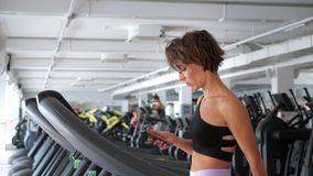 Η φίλαθλη γυναίκα εκπαιδεύει treadmill στη γυμναστική και κοιτάζει στο smartphone φιλμ μικρού μήκους